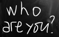 """Who are you"" handwritten with white chalk on a blackboard"